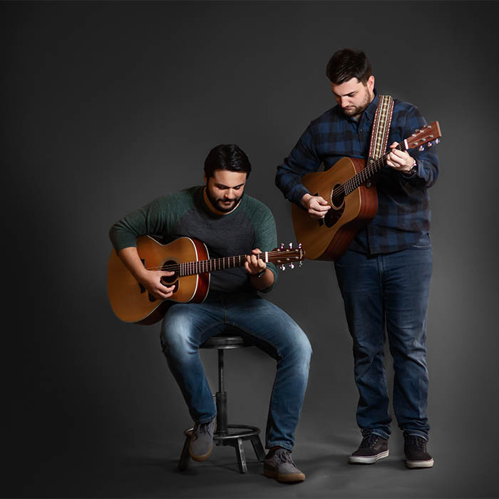 Dylan and Mike playing acoustic guitars
